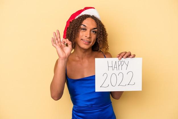 Młoda kobieta transseksualna łacińska świętuje nowy rok na białym tle na żółtym tle wesoły i pewny siebie, pokazując ok gest.