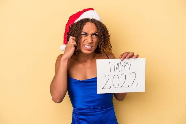 Młoda kobieta transseksualna łacińskiej świętuje nowy rok na białym tle na żółtym tle obejmujące uszy rękami.