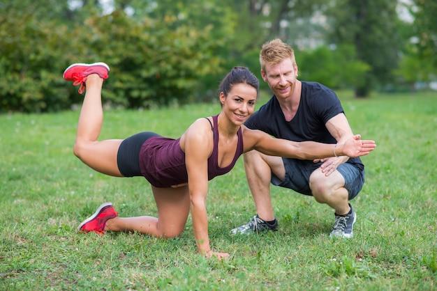 Młoda kobieta trening z jej osobistym trenerem w parku