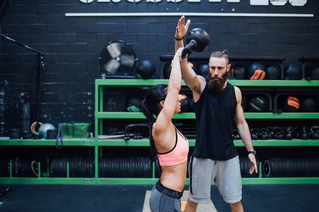 Młoda kobieta trenująca z kettlebell wspomagana przez osobistego trenera