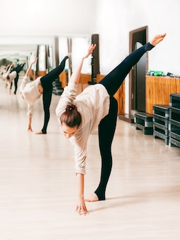 Młoda kobieta trenuje elastyczność. zajęcia taneczne.