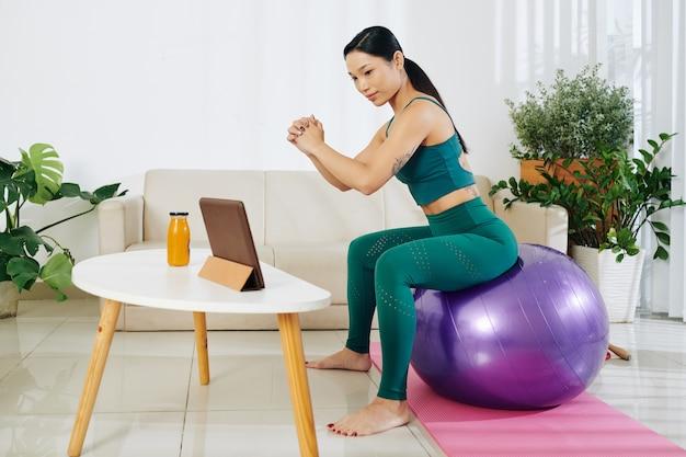 Młoda kobieta trenuje na piłce fitness w domu podczas oglądania samouczka na cyfrowym tablecie