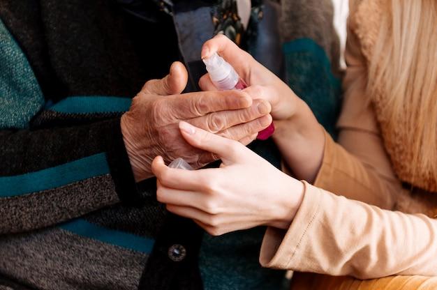 Młoda kobieta trenuje starszą babcię, aby traktowała swoje ręce antyseptycznie podczas okresu kwarantanny pandemii koronawirusa