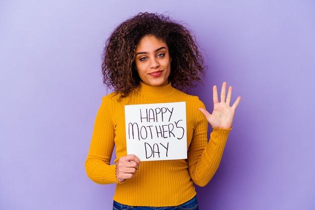 Młoda kobieta trzyma afisz dzień szczęśliwego matki na białym tle uśmiechnięty wesoły pokazując numer pięć palcami