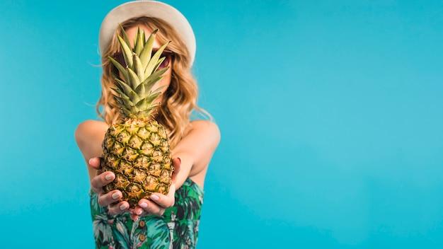 Młoda kobieta trzyma ananasa w kapeluszu i okularach przeciwsłonecznych