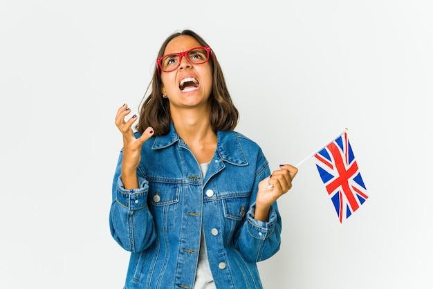 Młoda kobieta trzyma angielską flagę na białym tle na białej ścianie, podnosząc pięść po zwycięstwie, koncepcja zwycięzcy