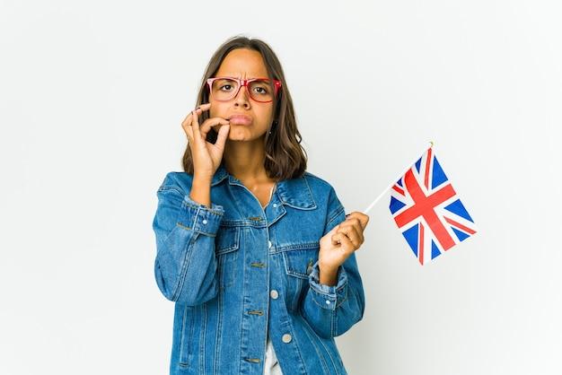 Młoda kobieta trzyma angielską flagę z palcami na ustach, zachowując tajemnicę