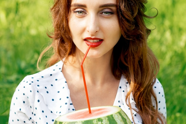 Młoda kobieta trzyma arbuza ze słomką blisko ust, siedząc na trawie na zewnątrz.