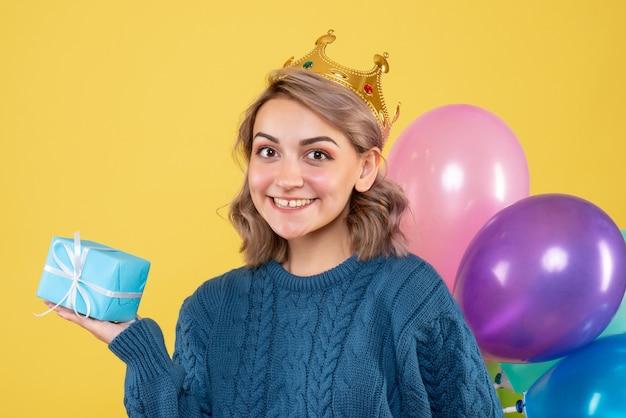 Młoda kobieta trzyma balony i mały prezent na żółto