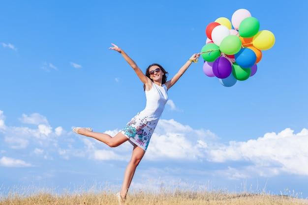 Młoda kobieta trzyma balony skaczące na polu w słoneczny dzień