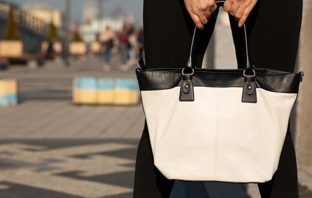 Młoda kobieta trzyma białą skórzaną torebkę. miejsce na tekst