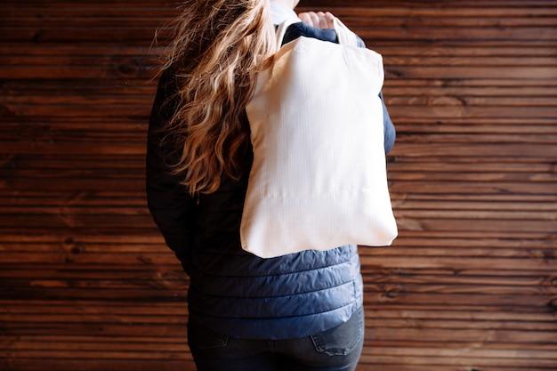 Młoda kobieta trzyma białą tekstylną eco torbę