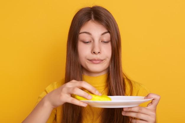 Młoda kobieta trzyma białego talerza na rękach z prostym włosy i wyciera je gąbką, patrzeje naczynie, stoi przeciw kolor żółty ścianie, studencki dziewczyny cleaning po obiadu.
