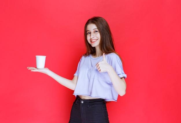 Młoda kobieta trzyma biały kubek na wodę i pokazuje znak satysfakcji.