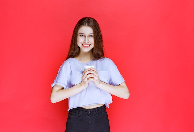 Młoda kobieta trzyma biały kubek wody jednorazowego użytku.