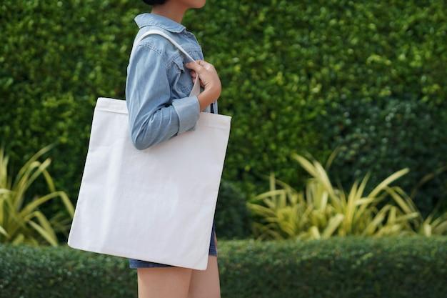 Młoda kobieta trzyma biały tkaniny torby odprowadzenie w parku