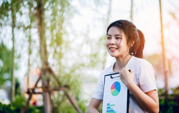 Młoda kobieta trzyma biznes wykres