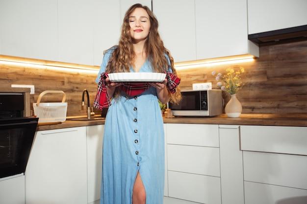 Młoda kobieta trzyma blaszkę z pyszne słodycze lub mięso. wnętrze kuchni domowej. kobieta biorąc blachę do pieczenia. koncepcja domowej roboty gotowania.