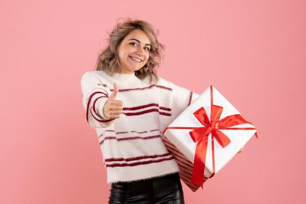 Młoda kobieta trzyma boże narodzenie obecny na różowo
