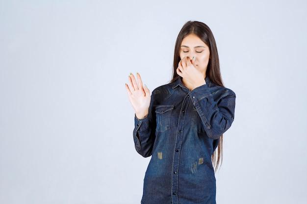 Młoda kobieta trzyma brodę z powodu nieprzyjemnego zapachu