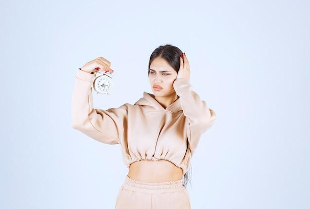 Młoda kobieta trzyma budzik i zasłaniając uszy