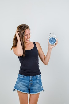 Młoda kobieta trzyma budzik w podkoszulek, spodenki i patrząc zdezorientowany, widok z przodu.