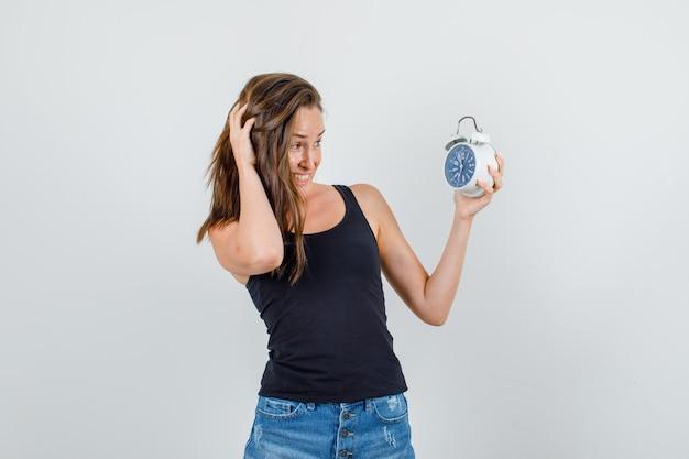 Młoda kobieta trzyma budzik w podkoszulku, spodenkach i wygląda niespokojnie. przedni widok.