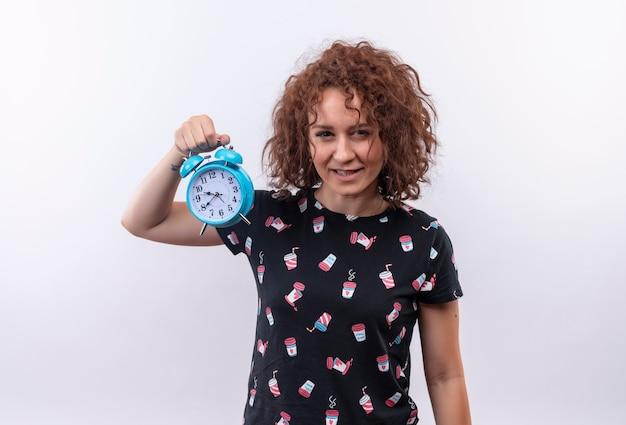 Młoda kobieta trzyma budzik z krótkimi kręconymi włosami