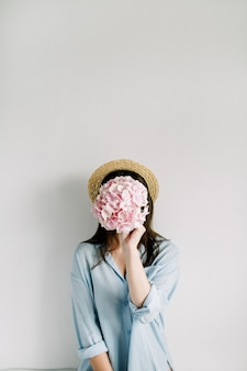 Młoda kobieta trzyma bukiet kwiatów różowej hortensji na białej powierzchni.