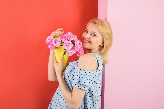 Młoda kobieta trzyma bukiet kwiatów szczęśliwa emocjonalna kobieta trzyma kwiaty piękna dziewczyna w modnej sukience
