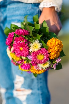 Młoda kobieta trzyma bukiet kwiatów w ręku poza