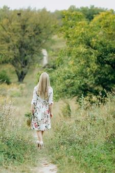 Młoda kobieta trzyma bukiet polne kwiaty
