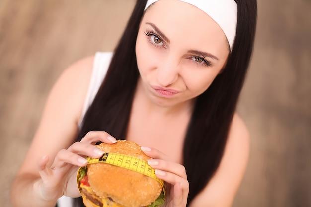 Młoda kobieta trzyma burgera i miarkę