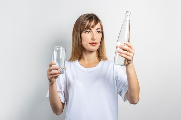 Młoda kobieta trzyma butelkę i szklankę z czystą wodą na jasnej powierzchni