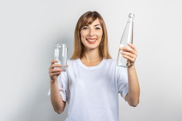 Młoda kobieta trzyma butelkę i szklankę z czystą wodą na jasnym tle