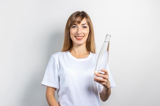 Młoda kobieta trzyma butelkę z czystą wodą na jasnym tle