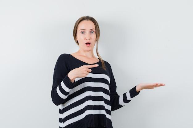 Młoda kobieta trzyma coś pod ręką i wskazuje na to w czarnej bluzce i czarnych spodniach i wygląda na zaskoczoną