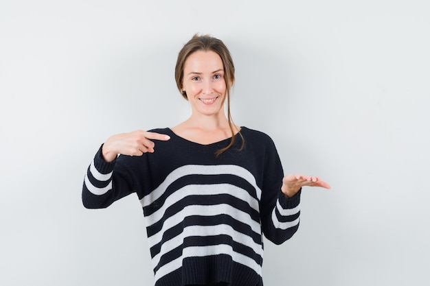 Młoda kobieta trzyma coś pod ręką wyimaginowanej i wskazując na to w czarną bluzkę i czarne spodnie i patrząc szczęśliwy