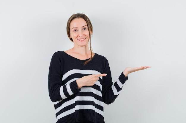 Młoda kobieta trzyma coś wyimaginowanego i wskazuje na to w pasiastej dzianinie i czarnych spodniach i wygląda na szczęśliwą