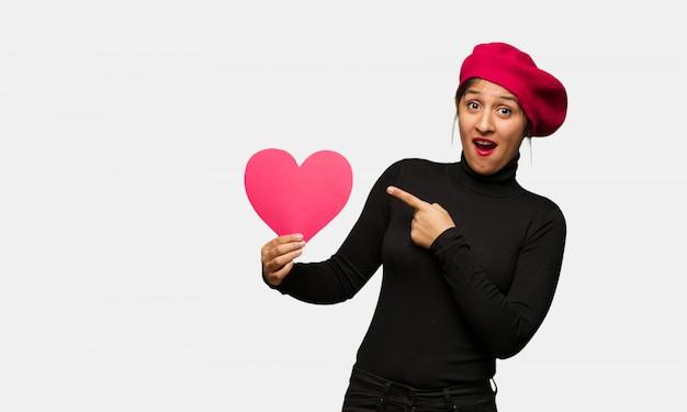 Młoda kobieta trzyma coś z ręką w valentines dniu