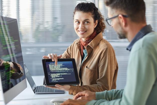 Młoda kobieta trzyma cyfrowy tablet i pokazuje swojemu koledze nowe oprogramowanie na ekranie podczas pracy w zespole