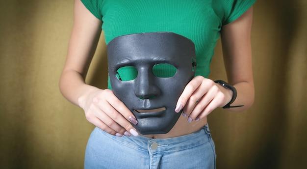 Młoda kobieta trzyma czarną maskę. fałszywe, anonimowe