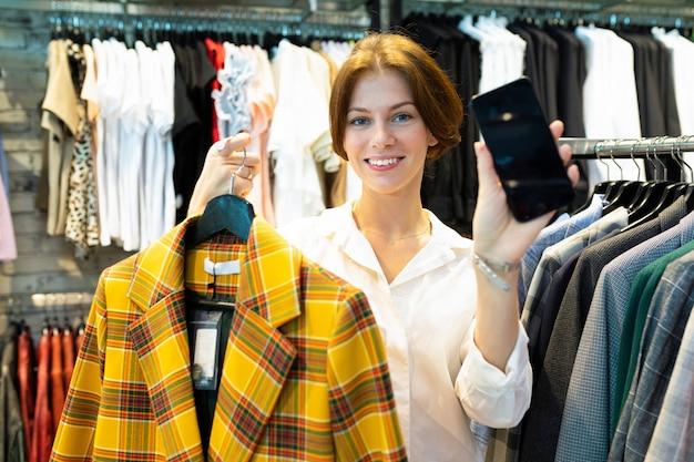Młoda kobieta trzyma czarny telefon i płaszcz w kratkę koloru żółtego w sklepie odzieżowym dla kobiet