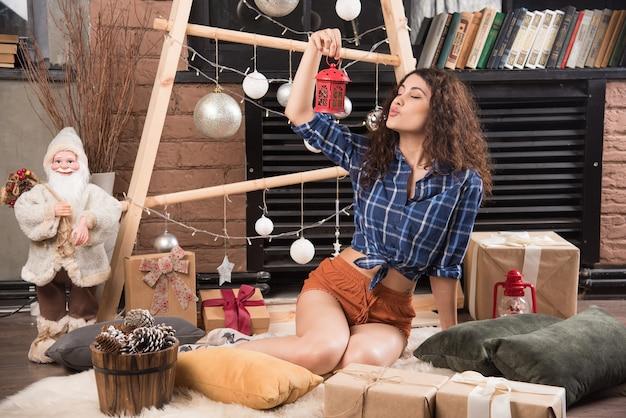 Młoda kobieta trzyma czerwoną lampkę bożonarodzeniową