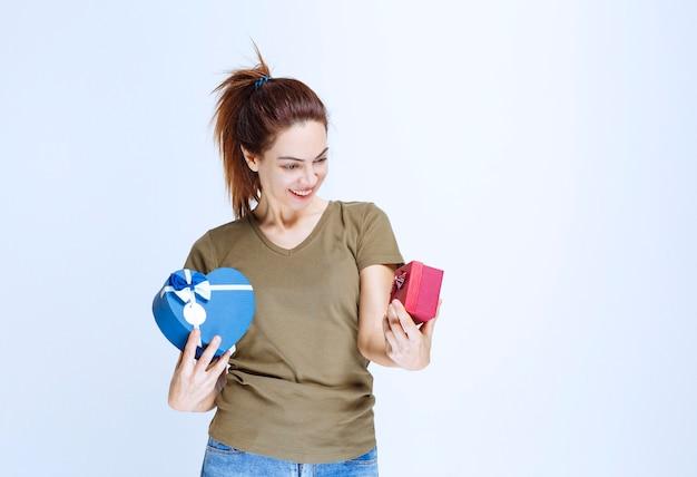 Młoda kobieta trzyma czerwone i niebieskie pudełka na prezenty w kształcie serca i cieszy się nimi