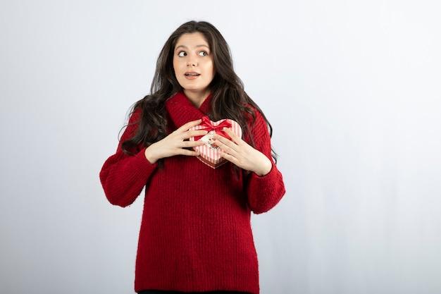 Młoda kobieta trzyma czerwone pudełko w kształcie serca na białym tle na białej ścianie.