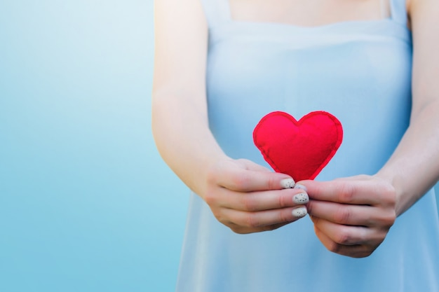 Młoda kobieta trzyma czerwonego serce w jej rękach na błękicie