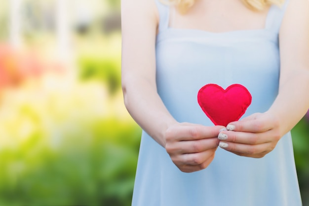 Młoda kobieta trzyma czerwonego serce w ona ręki