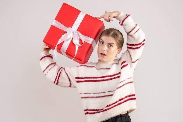 Młoda kobieta trzyma czerwony obecny na białym tle