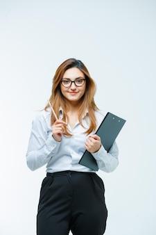 Młoda kobieta trzyma długopis i schowek